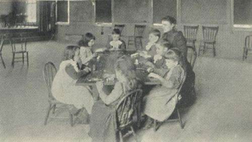 Seven children and a teacher sit around a table.