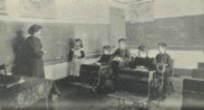 A teacher and a girl stand at a blackboard.  Four boys sit at their desks.