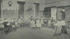 A group of boys and girls in a semi-circle engaged in sewing.
