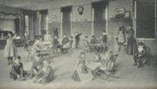 Childern in a large room, some sitting and others standing.