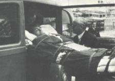 The author, strapped on a stretcher, enters an automobile.