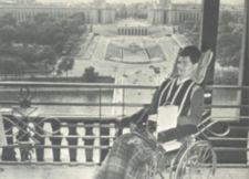 With Paris in the background, the author smiles from his wheelchair.