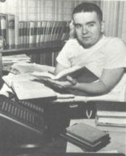 A young man with many books and a speaker phone.