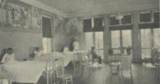 A hospital ward with three boys in beds, one boy sitting, and anurse standing.