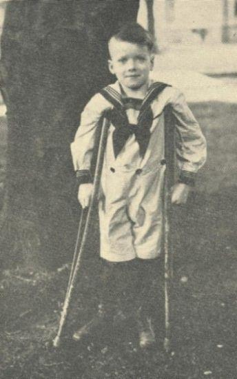 A young boy dressed in a sailor's suits stands with crutches and smiles.
