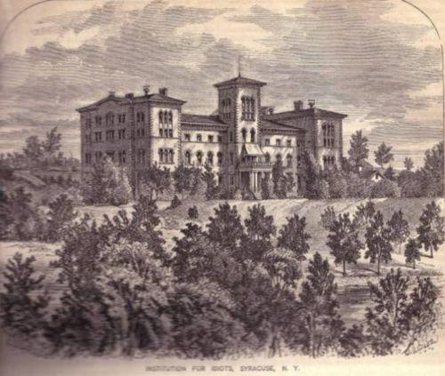 A large, ornate institutional building with trees in the foreground.