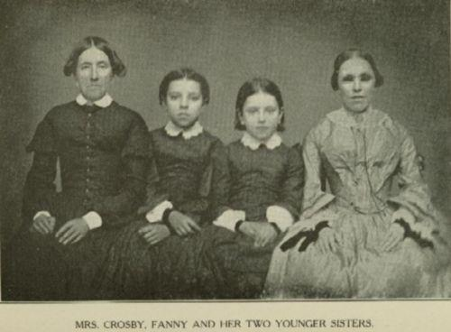 A photographic portrait of a women in a plain black dress with her three daughetrs, one wearing dark glasses.