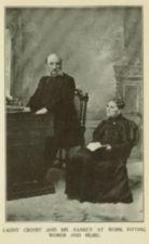 A man sits at a organ, and a woman in dark glasses holds a book.