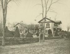 A large house with fence and elm trees.