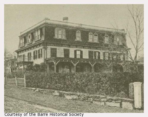 A three-story building with porch and hedges.