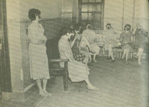 Seven women, most barefoot, sit on benches in a room.
