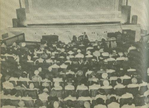 People sit in the rows of a small theater.