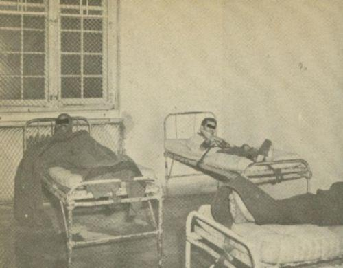 Three men restrained in beds.