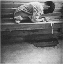 A boy tied to a wooden bench.