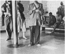 Partially dressed men standing on a tile floor.