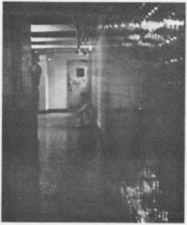 A man sitting on the floor at the end of a hall.
