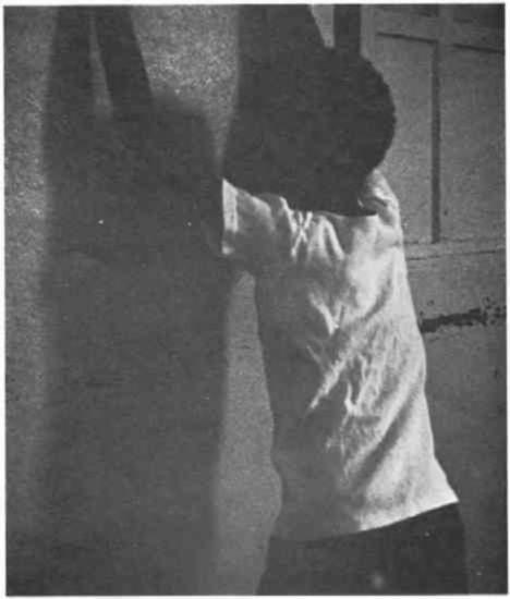 A young African-American man with his hands up on a wall.