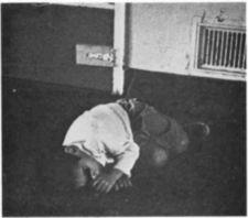 An African-American boy lying on the floor next a metal door.