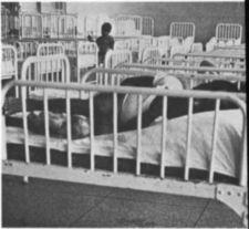 A child lying in bed with side rails in a room filled with identical beds.
