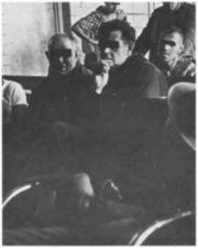 Men on a ward, some sitting on a bench.