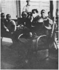 Men in chairs on a ward.