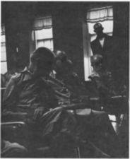 Men on a ward, one stands near a window.