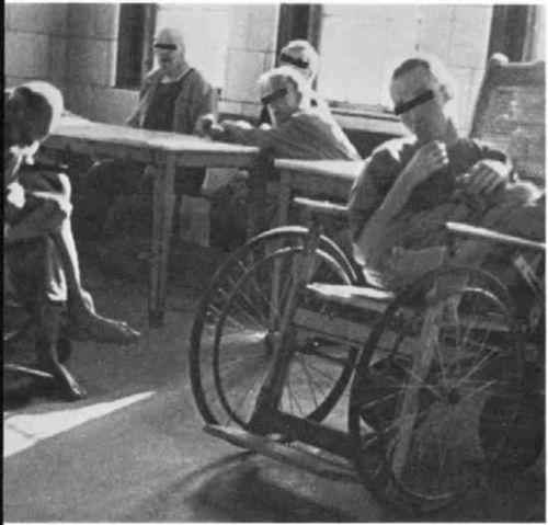 Men in a ward, some around a table, one in a wheelchair.