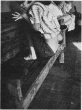 Woman crouching on a wooden bench.