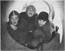 Three boys playing inside large pipe.