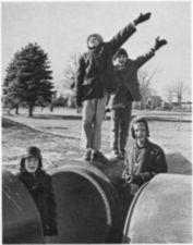 Three boys near large pipes, two saluting.