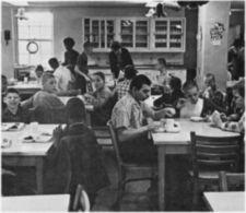 Children eating in a small dining hall.