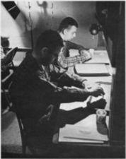 Two young men sitting at a table with trays.