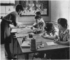 A woman helping four children working on art.