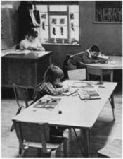 A teacher at her desk and two children at tables.