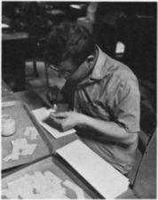 A young man gluing paper.