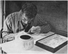 A young man cutting paper.