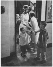 Women and children coming through a door.