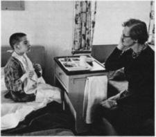 A boy sits on a bed with a tray of food and speaks with a woman.