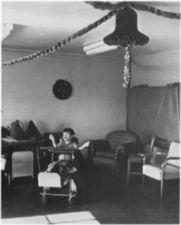 A boy in a room with Christmas decorations.