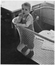 A boy in a playpen.