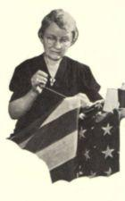An elderly woman sewing an American flag.
