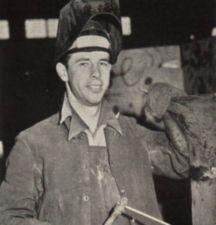 A man wearing a welding shield.