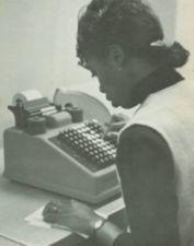 An African American woman working on an adding machine.