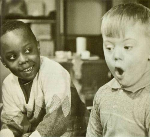 Two boys, One African American and the other white.  One smiles and the other appears to be singing.