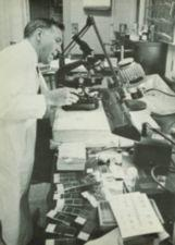 A man in a white lab coat works at a microscope.