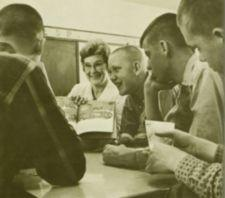 A woman showing a Dr. Seuss book to four teenage boys.