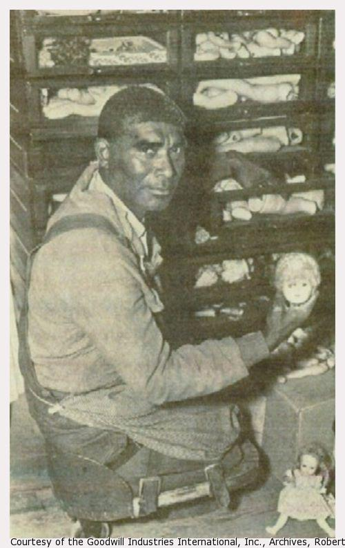 An African African man, a double amputee, works on a case of broken dolls.