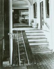 Wooden ramp along stairs in ornate Victorian house.