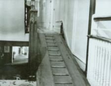 Ramp covering stairs next to ornate woodwork.