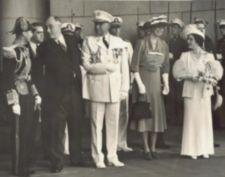 Roosevelt, holding the arm of a man in uniform, speaks with the King.  Eleanor Roosevelt and Queen Elizabeth stand nearby.